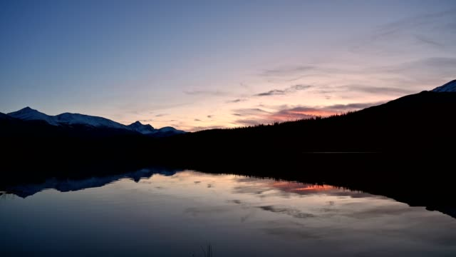 patricia lake with mountain range and sunset sky reflection in jasper national park - wilderness stock videos & royalty-free footage