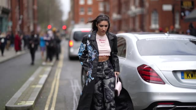 patricia manfield wears a white cropped and ripped tshirt a black long leather coat with blue floral print gray pants with printed dragons a bag a... - hair care stock videos & royalty-free footage