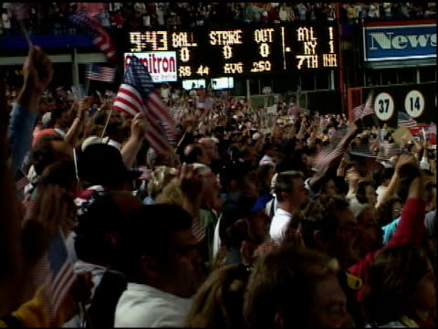 ws patriotic baseball fans standing in bleachers shouting usa and waving american flags at shea stadium at first mlb baseball game after september 11... - shea stadium stock videos and b-roll footage