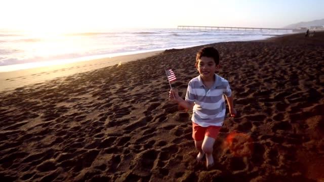 vidéos et rushes de boy patriotique avec drapeau américain sur la plage - lenteur