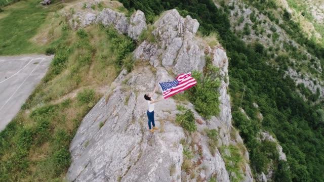patriotic woman holding u.s. flag in mountains - patriotism stock videos & royalty-free footage