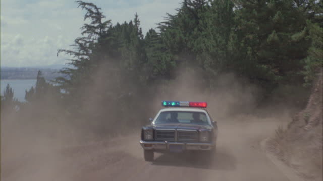 A patrol car speeds along a dusty mountain road with its lights flashing.