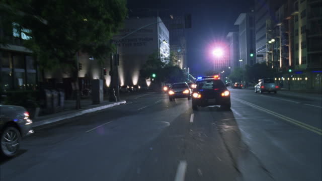 A patrol car speeds through traffic with its biz-bar flashing.