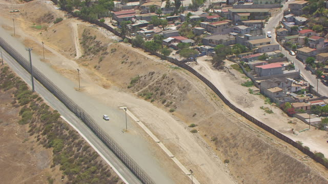 WS ZO AERIAL POV Patrol vehicle parked near international border fence between Tijuana Mexico and San Diego / San Diego, California, United States