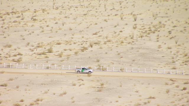 WS TS AERIAL POV Patrol vehicle travelling through dirt road along border fence between California and Mexico / California, United States