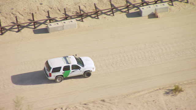 WS TS ZI ZO AERIAL POV Patrol vehicle travelling through unpaved desert road along border fence between California and Mexico / California, United States