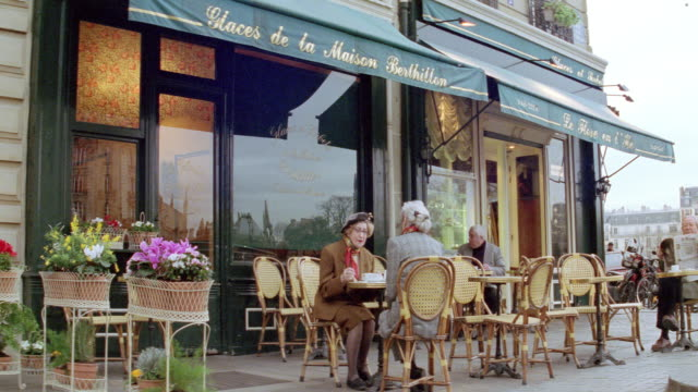 patrons dine alfresco at a sidewalk cafe in paris. - francia video stock e b–roll