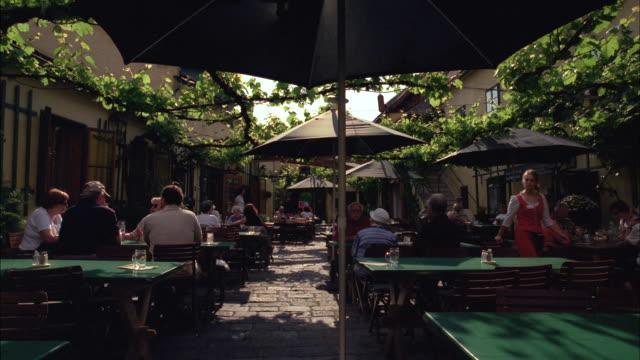 patrons dine at a sidewalk cafe in vienna, austria. - österreich stock-videos und b-roll-filmmaterial
