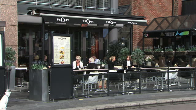 Patrons enjoy coffee at an outdoor cafe in Oslo, Norway.