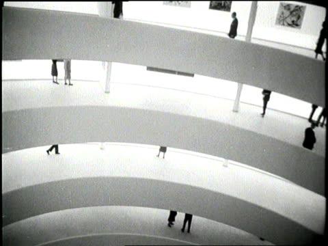 patrons enjoy the paintings in the guggenheim museum in new york city. - 1959年点の映像素材/bロール