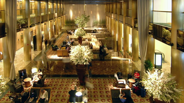 t/l patrons sitting and walking around busy hotel lobby / new york city, new york, united states - lobby stock videos & royalty-free footage