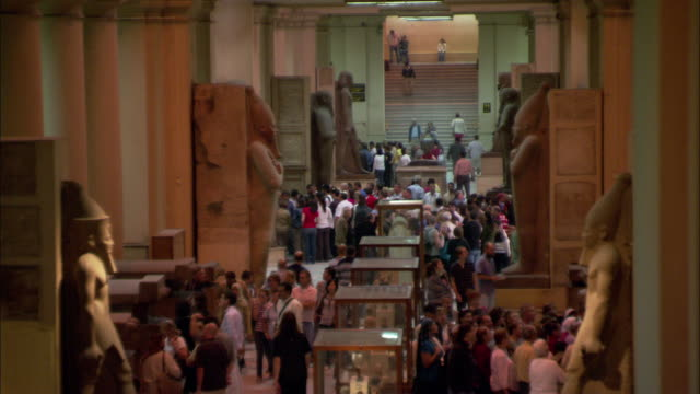 patrons tour a large museum exhibit of ancient egypt. - arte dell'antichità video stock e b–roll