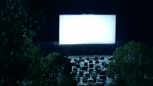 patrons walk in between cars parked at a drive-in movie theater. - projection screen stock videos & royalty-free footage