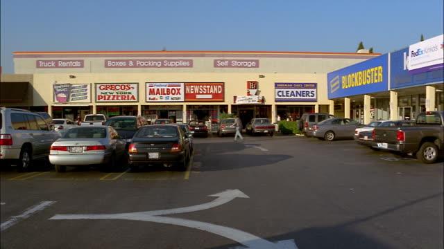 patrons walk through the parking lot at a shopping center in sherman oaks, california. - sherman oaks stock videos & royalty-free footage