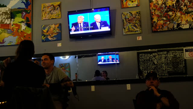 patrons watch on television at a bar as united states republican president donald j. trump and democratic opponent former vice president joe biden... - debatte stock-videos und b-roll-filmmaterial