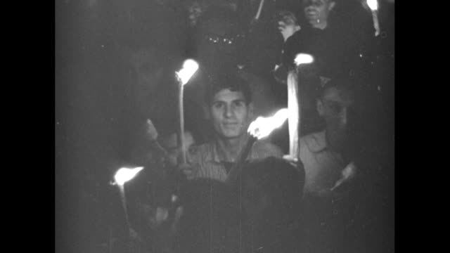 vidéos et rushes de pattern of lights on wall of building / overhead shot of young men carrying lighted torches at night in st. peter's square / close view of young men... - prêtre