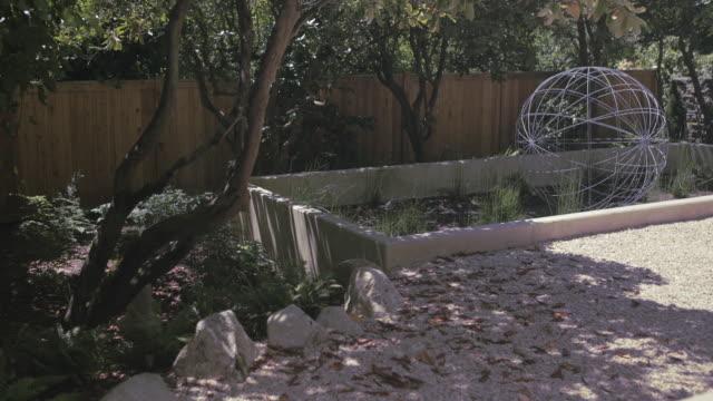 patterns of dappled light move across rocks in garden. - dappled light stock videos and b-roll footage