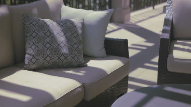Patterns of light shift across outdoor furniture on veranda.