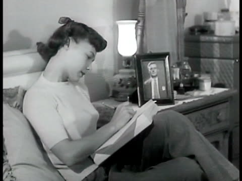 dramatization 'patti' writing letter to boyfriend cu letter telling albert that things are looking up in modeling but she gets lonesome for him... - anno 1950 video stock e b–roll