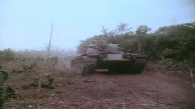 vídeos de stock, filmes e b-roll de patton tank driving down road with soldiers patrolling alongside / vietnam - formato letterbox