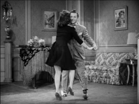 b/w 1946 patty lacey & ray hirsch dancing with protruding buttocks in living room / short film - couple relationship videos stock videos & royalty-free footage