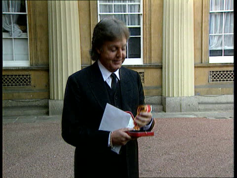 paul and linda mccartney paul and linda mccartney lib buckingham palace ms paul mccartney posing with medal outside palace - paul mccartney stock videos and b-roll footage
