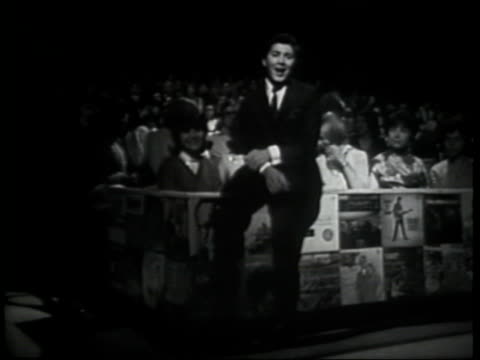 vídeos de stock, filmes e b-roll de paul anka introduces hullabaloo london segment audience full of caucasian teenagers seated behind him - espetáculos de variedade