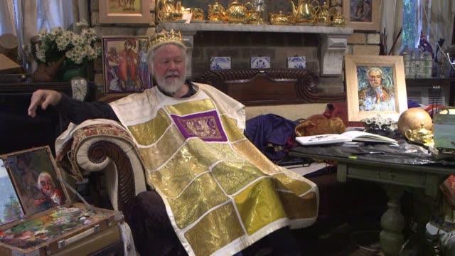 Paul Delprat de 76 anos viste una tunica bordada y lleva una corona dorada en la cabeza