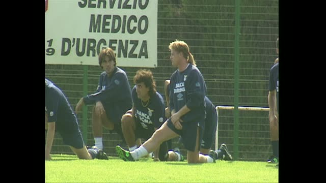 paul gascoigne stretching and warming up at training session with ss lazio fc 1993, has ponytail mullet hairstyle - ラツィオ州点の映像素材/bロール