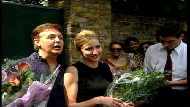 paul mccartney and heather mills divorce case: heather mills sues press; ext sir paul mccartney posing next mills holding bouquets of flowers after... - フリーズフレーム点の映像素材/bロール