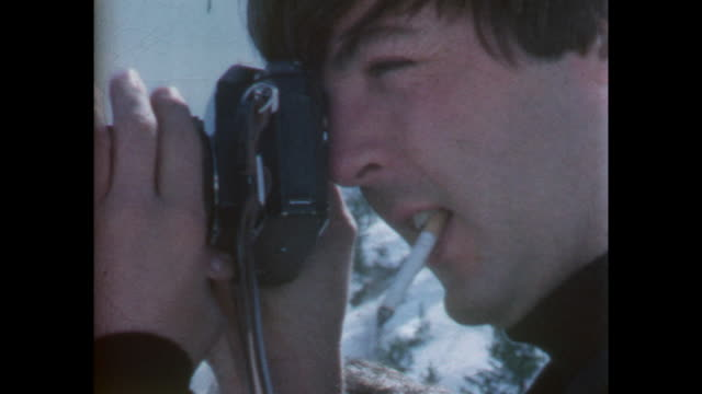 Paul McCartney is taking a photograph with a 35mm camera while holding and smoking a cigarette / 8mm amateur home movie footage filmed by the actor...