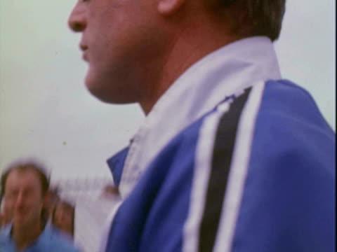vídeos de stock, filmes e b-roll de paul newman driving canam racecar along winding empty racetrack paul newman wearing racing helmet smiling and chatting with crew / mr newman dons... - artigo de vestuário para cabeça