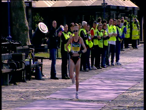 paula radcliffe running on cobbles past line of cheering stewards, head begins to wobble, women's elite race, 2002 london marathon - sportlerin stock-videos und b-roll-filmmaterial