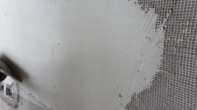 pave the putty powder on the wall with nylon mesh net in slow motion - mesh textile stock videos & royalty-free footage