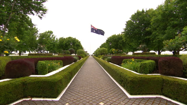 Paved path highlighted by a white border red and green manicured hedge garden leads the way to a flag pole flying the Australian flag