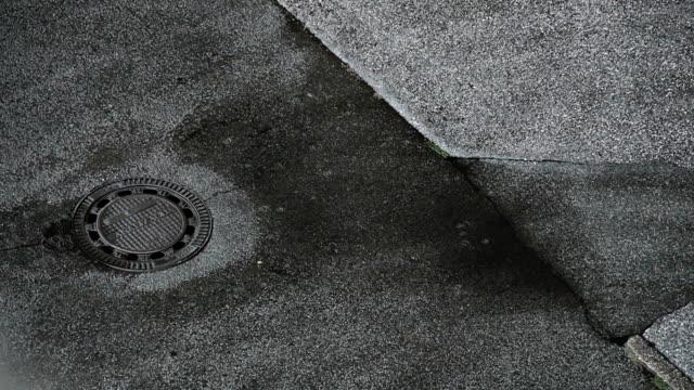 vídeos y material grabado en eventos de stock de pavimento y lluvia - tapadera de cloaca