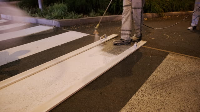 pavement marking crew repainting zebra crossing at dusk - crossing stock videos & royalty-free footage