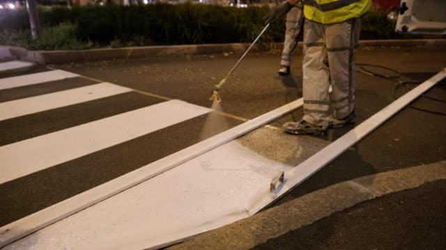 pavement marking crew repainting zebra crossing at dusk - freshly painted stock videos & royalty-free footage