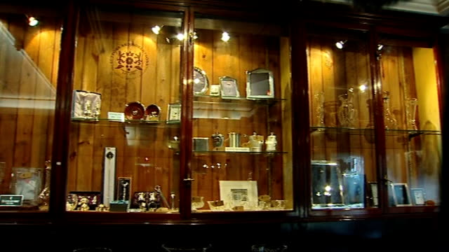 pawnbroker's shop sterling silver items in display case / general view of display case / watch and jewellery repairs sign on glass door / clocks on... - pawnbroker stock videos & royalty-free footage