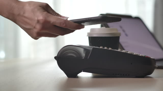 paying by contactless payment on smart phone at cafe - money back guarantee stock videos & royalty-free footage