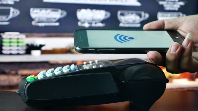 Paying by Contactless payment with Smart phone in Cafe, NFC technology to pay