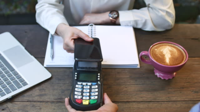 vídeos de stock e filmes b-roll de paying contactless payment in coffee shop with laptop - pagar