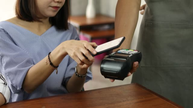paying through smartphone using nfc technology, contactless payment - contactless payment stock videos & royalty-free footage