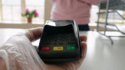 Paying with my phone. Contactless payment with NFC technology at a small shop during the COVID-19 pandemic. Wearing protective gloves at work and while in the city.