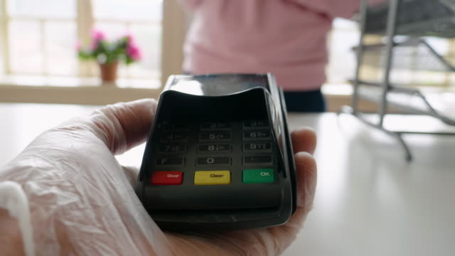 paying with my phone. contactless payment with nfc technology at a small shop during the covid-19 pandemic. wearing protective gloves at work and while in the city. - retail place stock videos & royalty-free footage