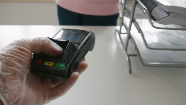 paying with my phone. contactless payment with nfc technology at a small shop during the covid-19 pandemic. wearing protective gloves at work and while in the city. - paying stock videos & royalty-free footage