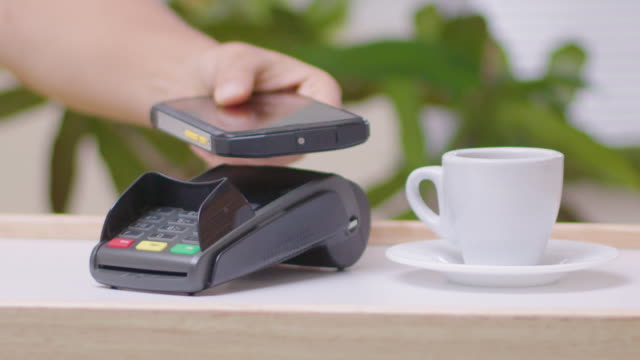 paying with my phone. contactless payment with nfc technology at a small coffee shop during the covid-19 pandemic. social distancing to flatten the curve. - flatten the curve stock videos & royalty-free footage