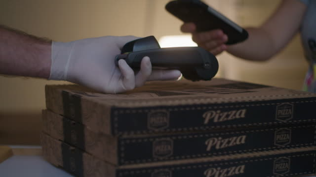 paying with my phone. contactless payment with nfc technology at a pizza shop during the covid-19 pandemic. wearing protective gloves at work to flatten the curve and protect one self. - flatten the curve stock videos & royalty-free footage
