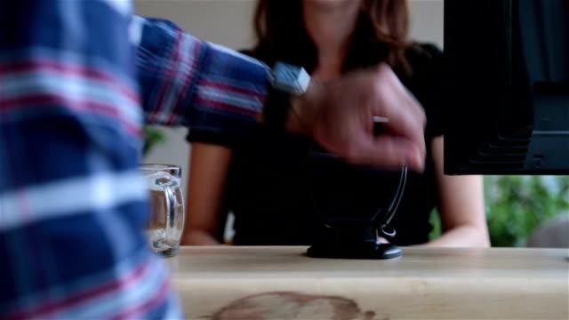 vídeos de stock, filmes e b-roll de pagar com tecnologia nfc na smartwatch na coffee shop - relógios de pulso