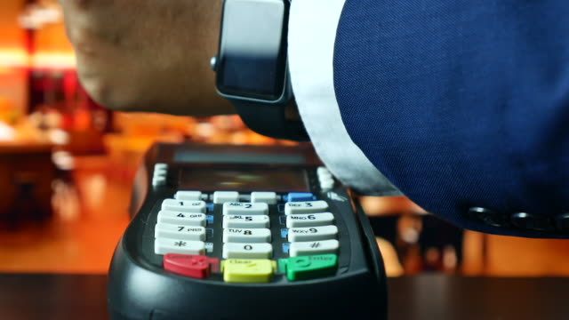 vídeos de stock e filmes b-roll de paying with nfc technology on smart watch in the restaurant, contactless payment - relógio de pulso